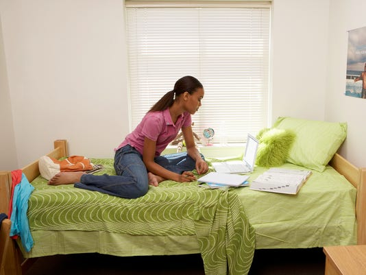 Young woman sitting on bed with laptop and books in student dormitory