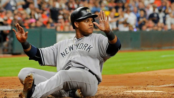 New York Yankees' Starlin Castro slides safely at home to score a run on Aaron Hicks' three-run triple during the fifth inning of a baseball game against the Houston Astros, Tuesday, July 26, 2016, in Houston.