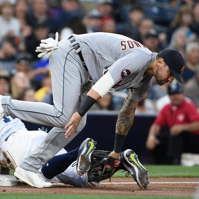 Tigers' Nicholas Castellanos dives for the throw as