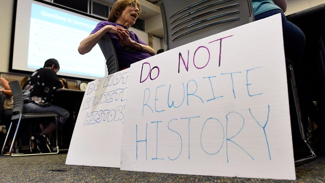 """A woman in the audience displays signs that read """"Do Not Rewrite History,"""" at the Michgan Department of Education forum in Waterford Township on Wednesday."""
