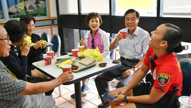 "Officer Joneen Terlaje, right, laughs during Guam Police Department's ""Coffee with a Cop"" outreach event at the Tamuning McDonald's restaurant on Jan. 25, 2017. Terlaje was laughing at comments such as, police officers are usually scary, and a question on whether she was married."