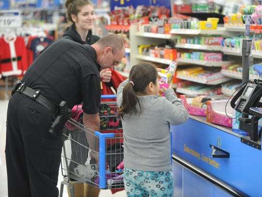 Sgt. John Lackey unloads a cart during a previous Shop with an Officer event at Wal-Mart.