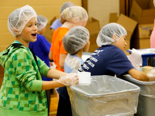 A Belle Sherman student scoops rice at the Feed My