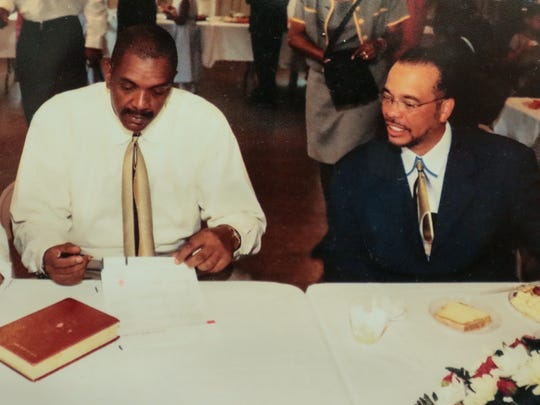 The Rev. Edgar Scott, left, and the Rev. Dr. Ronnie Williams look at a contract to build a new sanctuary, during an event in August 2001 at Generostee Baptist Church in Starr.