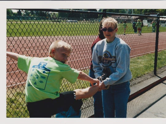 Thomas Chiapella runs in the 1999 Awesome 3000. His sister, Nicole, helps him stretch. Chiapella says the annual event is what first exposed him to running.