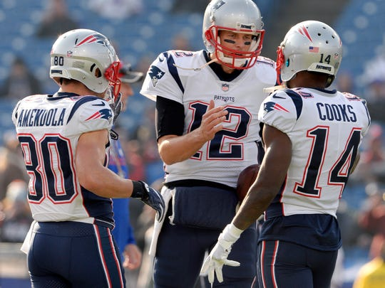 FILE - In this Dec. 3, 2017, file photo, New England Patriots quarterback Tom Brady (12) talks with wide receivers Brandin Cooks (14) and Danny Amendola (80) before an NFL football game against the Buffalo Bills in Orchard Park, N.Y. The Patriots and the Philadelphia Eagles are set to meet in Super Bowl 52 on Sunday, Feb. 4, 2018, in Minneapolis.