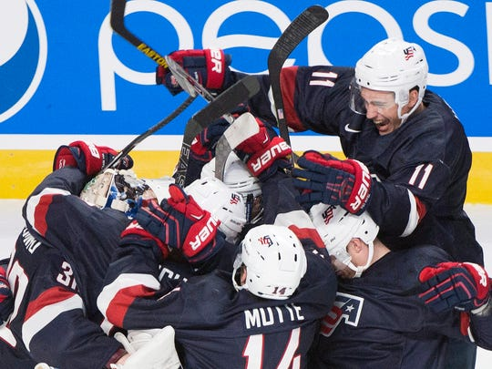 St. Clair native Tyler Motte celebrates with his teammates after the United States defeated Finland in the shootout of a preliminary round hockey game at the IIHF World Junior Championship in Montreal, Friday.