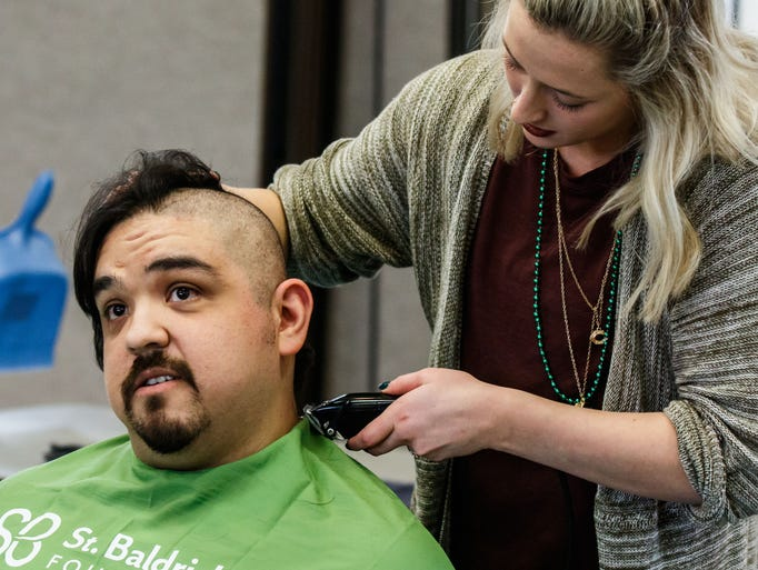 Stylist Lexi Norgal shaves the head of Luis Cruz of