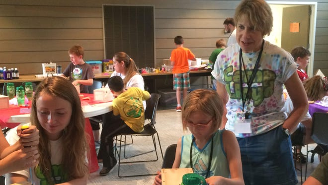 Camp Lloyd founder and director Illene Cupit, right, watches as campers, including 9-year-old Emma Henjum of Suamico, make wooden memory boxes during the first day of camp Monday at the University of Wisconsin-Green Bay's Mauthe Center.