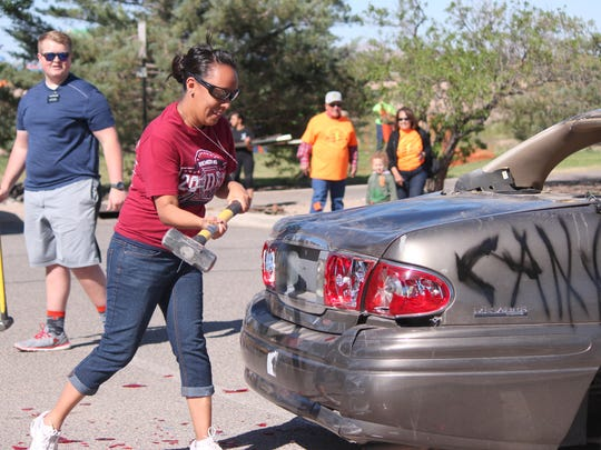Linda Baeza takes out her rage on thea car donated by the Deming Sisbarro Superstore at Saturday's 11th annual Celebration of Life Cancer Walk. Sisbarro donated the car so people could take a sledge hammer to it for a $1 donation. The proceeds all went to Cancer Support of Deming & Luna County, Inc.