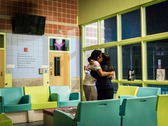 Tatianna (last name withheld),16, left, shares a hug