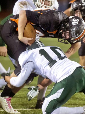 Middlebury's Justin Stone (topo) gets tangled up by St. Johnsbury's Devon Switser in the Division 1 football championship in Rutland on Saturday, November 8, 2014.