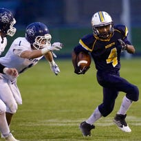 Sheboygan North's Kenyon Gilbert runs past a pair of Bay Port defenders in the first half on Friday night.