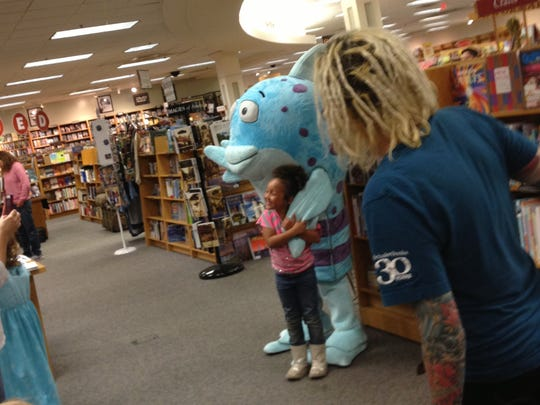 Madison Harris, 5, of Holt, gets a hug from Mr. Fish at the Pout-Pout Fish reading event at Schuler Books and Music at Meridian Mall.