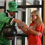 Fern Creek High Principal Nate Meyer, dressed as a leprechaun, hands a check to a student who had passed an Advanced Placement exam.
