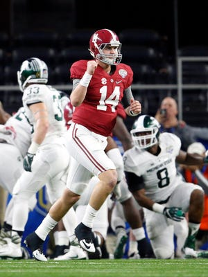 Alabama Crimson Tide quarterback Jake Coker (14) celebrates after a touchdown by running back Derrick Henry (not pictured) in the second quarter against the Michigan State Spartans in the 2015 CFP semifinal at the Cotton Bowl at AT&T Stadium.