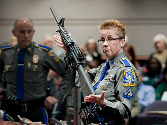 Firearms training unit Detective Barbara J. Mattson, of the Connecticut State Police, holds up a Bushmaster AR-15 rifle, the same make and model of gun used in the Sandy Hook School shooting, during a hearing of a legislative subcommittee in Hartford, Conn., Jan. 28, 2013.