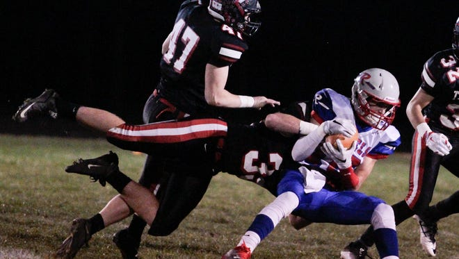 Jayden Williamson of East Central lays out and makes the tackle on Jacob Luedeman of Roncalli on Friday night. The Rebels defeated the Trojans in the semistate game at East Central High.