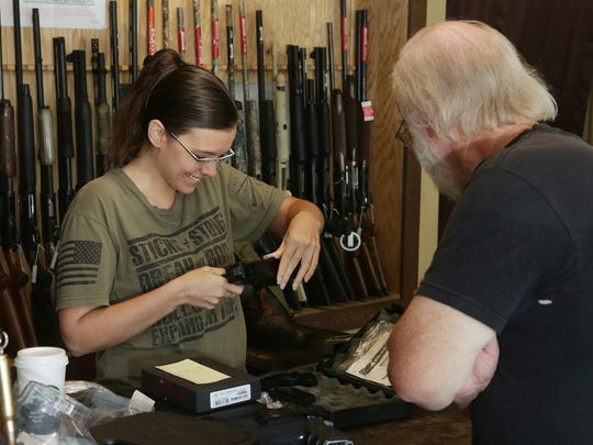Jessica Jones,  clerk at Armed Sources Gun & Pawn LLC, talks to customer Chris Cantrell.