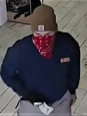 A security camera image shows one of two men who robbed