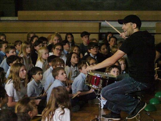Troy Kryzalka of Number Drummer Live shows students the joy of drumming.