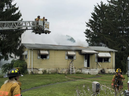 Firefighters spray water from an aerial ladder truck onto the roof of a house at 804 Strack's Dam Road on Monday afternoon. Jeremy Long—Lebanon Daily News