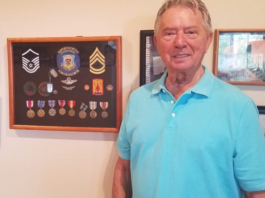 James Pallan Stands Proudly By A Collage Of His Medals