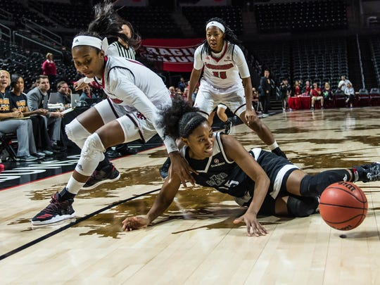 UL forward Kimberly Burton, left, goes for a loose ball against Arkansas State's Dominique Oliver (25) during the Cajuns' win Thursday at the Cajundome.
