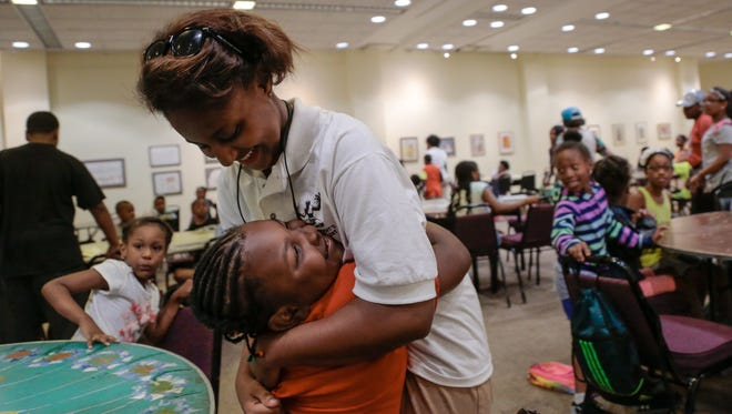 Monique Whittaker, 17, of Detroit, is hugged by Nakyia Moore while helping students during lunch at Camp Africa at the Charles H. Wright Museum of African American History in Detroit on Monday July 18, 2016 while working as a camp counselor through Grow Detroit's Young Talent program.