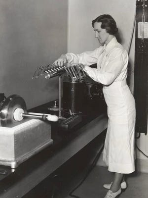 Dr. Margaret Pittman at the U.S. Institute of Health, demonstrates the Flosdorf-Mudd lyophile process, which dries cultures of meningitis germs.