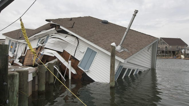 Adding to the destructive power of surge, battering waves may increase damage to buildings directly along the coast, such as this one in Tuckerton from superstorm Sandy.