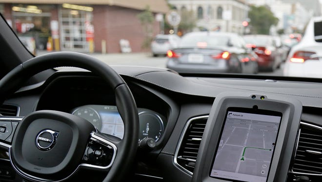 FILE - In this Dec. 13, 2016 file photo, an Uber driverless car waits in traffic during a test drive in San Francisco.