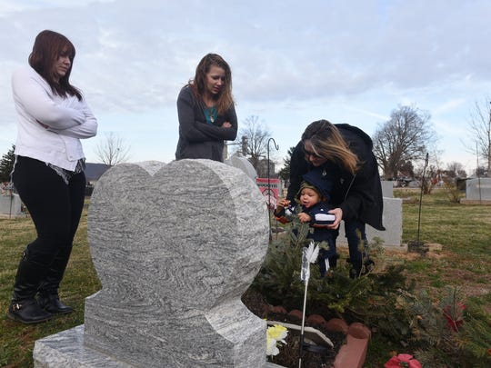 Holly Detty, left, Cassandra Detty, center, Christina Arredondo and Aviyon, Cassandra's son, visit Felicia Detty's grave Thursday, Feb. 16, 2017, in Chillicothe.