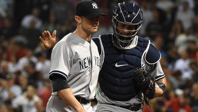 New York Yankees catcher Gary Sanchez (24) congratulates relief pitcher David Robertson (30) after pitching out of a jam during the eighth inning against the Boston Red Sox at Fenway Park on Saturday, Aug. 19, 2017.