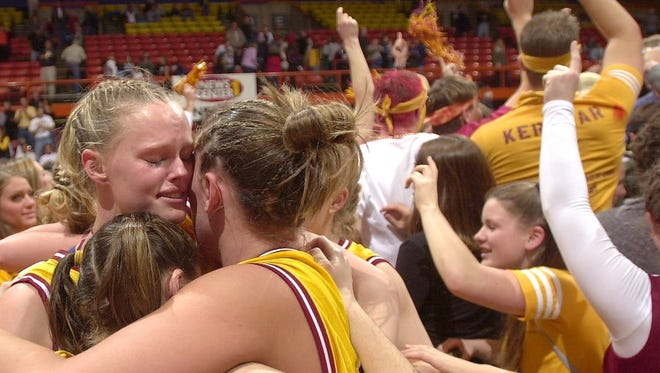 -While fans celebrate at rear, Roosevelt's Courtney Farrell, Erin Case (backs to camera) and Ashley Pederson embrace moments following winning their fourth straight class AA girls Basketball championship in Rapid City.