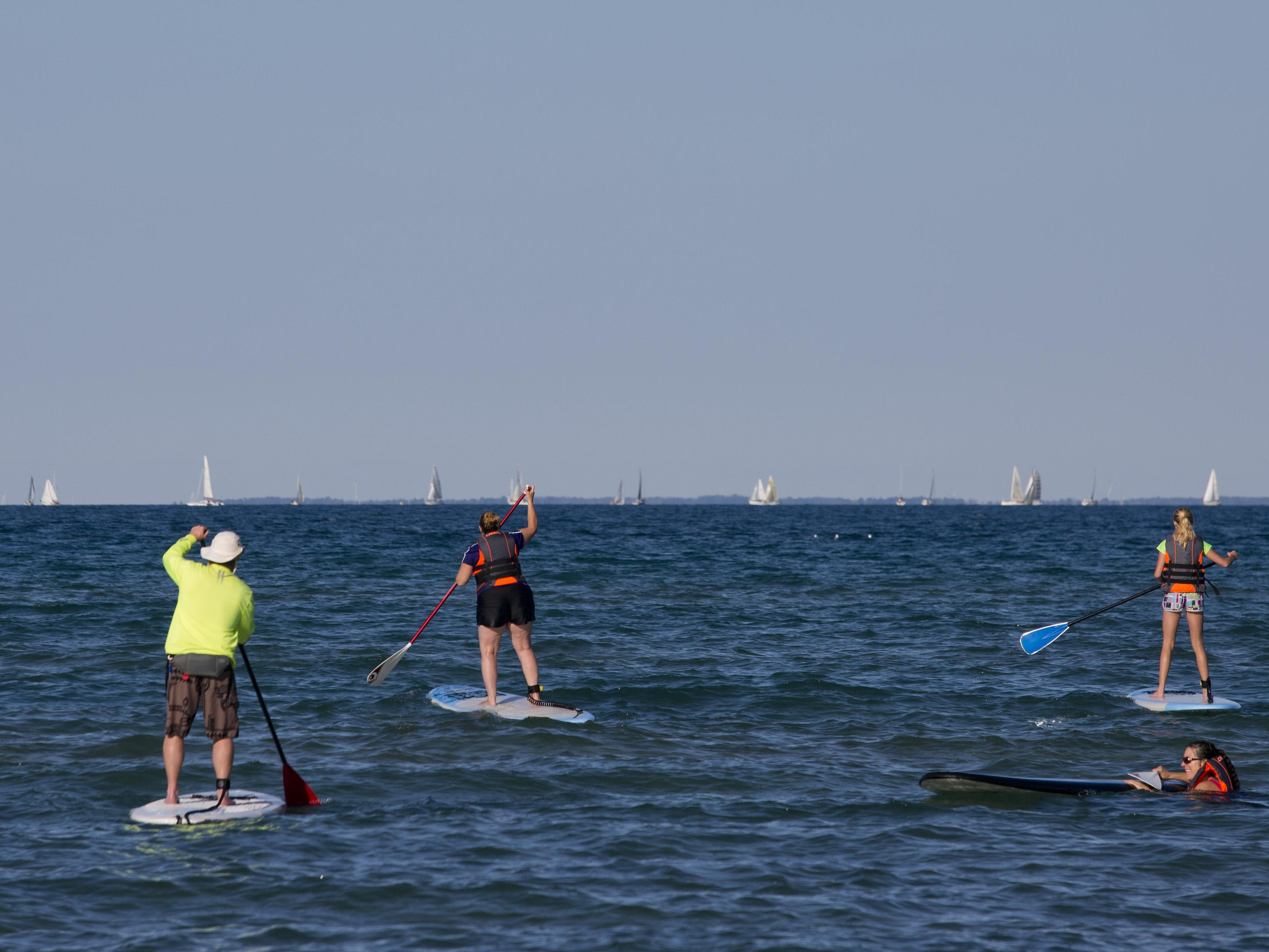 Participants head out on the lake during a stand up paddle board class Wednesday at Lakeside Beach in Port Huron.