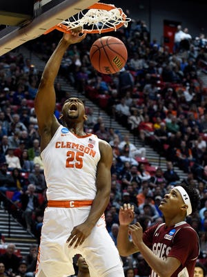 Clemson forward Aamir Simms (25) dunks as New Mexico State forward Jemerrio Jones (10) watches during the first half of a first-round NCAA college basketball tournament game Friday in San Diego.