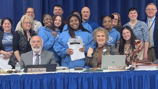 Students from the Boys and Girls Club's Keystone Club pose with Monticello district leaders and members of the Board of Education following their presentation.