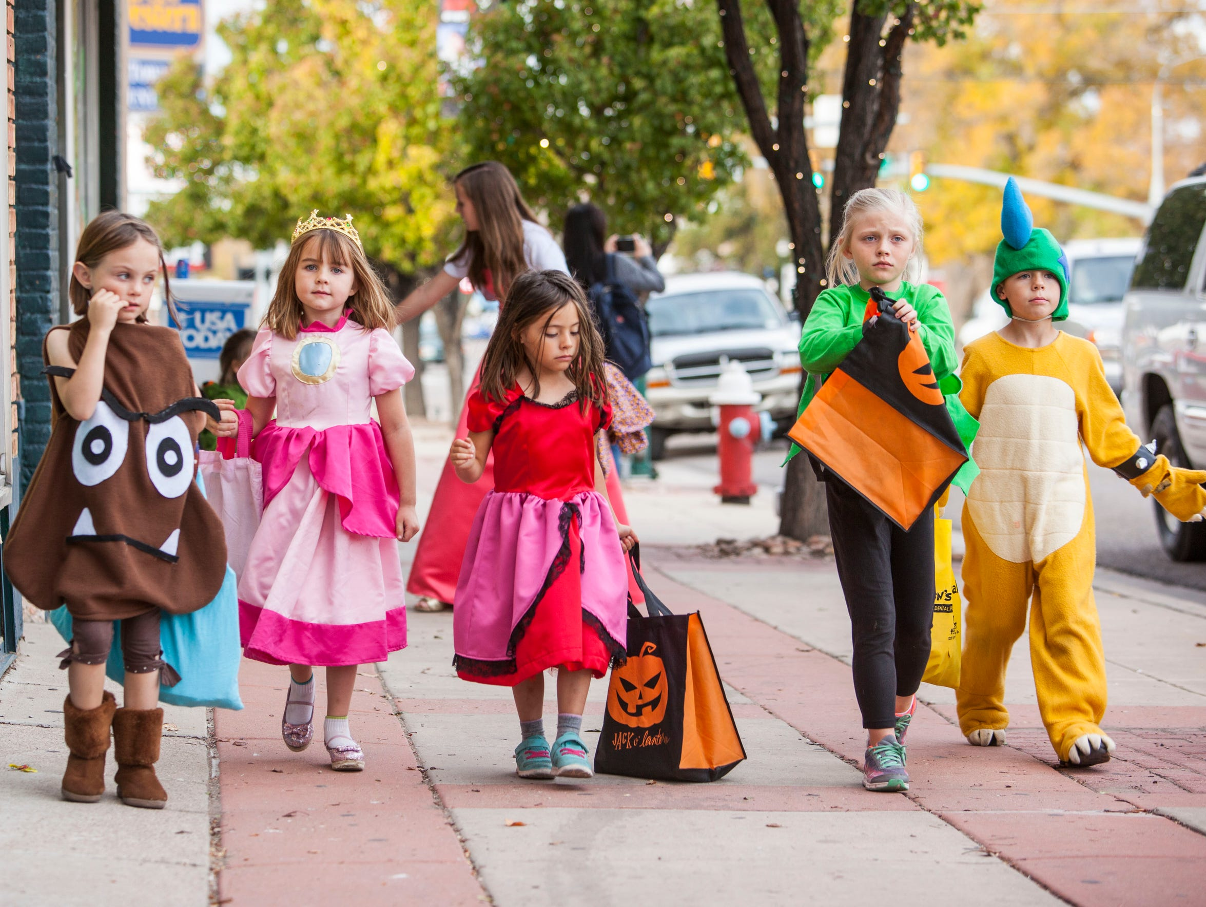Kids dressed in costumes walk along Main Street in