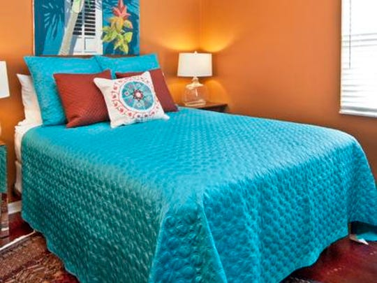 The strong terra cotta color in a guest bedroom makes a statement.