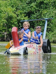 Savannah Davis, Matthew Johnson and Toryn Sontag all of croswell give it their all in their 13 boat during the cardboard boat races at the Swinging Bridge Festival in Croswell.