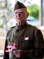 Ervin Shudarek, 88, wears his father's World War I uniform as he hands out flowers for National Poppy Day at the Copps grocery store in Plover, Wis., May 18, 2018. The poppies represent the sacrifices veterans have made for their country, and donations went to the American Legion.