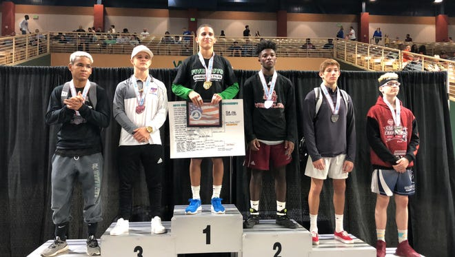 Fort Myers sophomore Chris Rivera stands atop the podium Saturday after winning the Class 2A 126-pound state title at Silver Spurs Arena in Kissimmee.