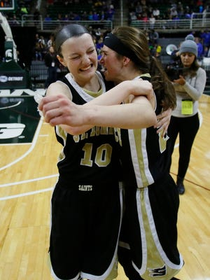 St. Ignace's Autumn Orm and Margo Brown hug each other as they celebrate their 64-60 overtime win over Pittsford in the MHSAA Class D girls basketball final on Saturday, March 21, 2015 in East Lansing.