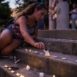 Paul Kieu/The Advertiser Lily Stagg lights candles on stage during a vigil for the victims of the Grand 16 Theatre Shooting on Saturday at Parc Sans Souci in Lafayette. Lily Stagg lights candles on stage during a candlelight vigil for the victims of the Grand 16 Theatre Shooting at Parc Sans Souci in Lafayette, La., Saturday, July 25, 2015.