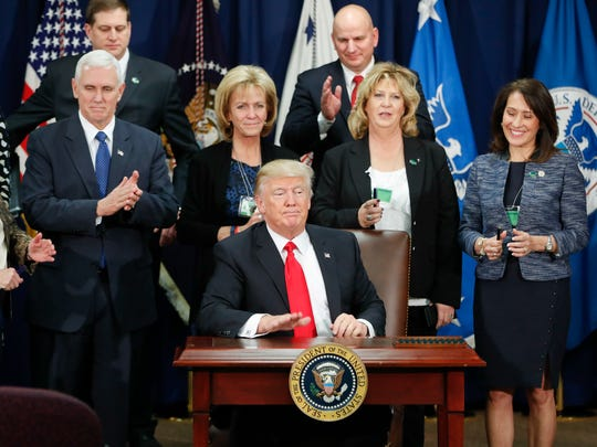 President Donald Trump taps on the table after signing an executive order Jan. 25, 2017, for immigration actions to build a border wall.