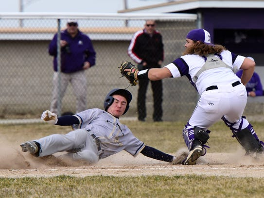 Fremont Ross catcher Noah Cook tries to block the plate Monday against Tiffin Columbian.