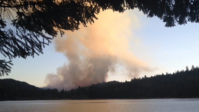The Reeves Creek  fire burned about 200 acres of drought-parched woods and threatened seven homes in a rural area about 15 miles southwest of Grants Pass, Ore. By Tuesday, a fire line was built around 70 percent of the fire, according to Oregon Department of Forestry.