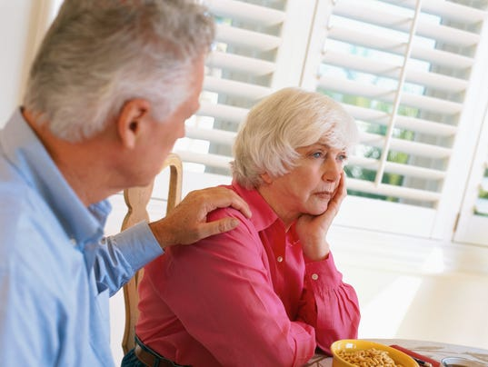 side view of an elderly man consoling his wife sitting at the dining table