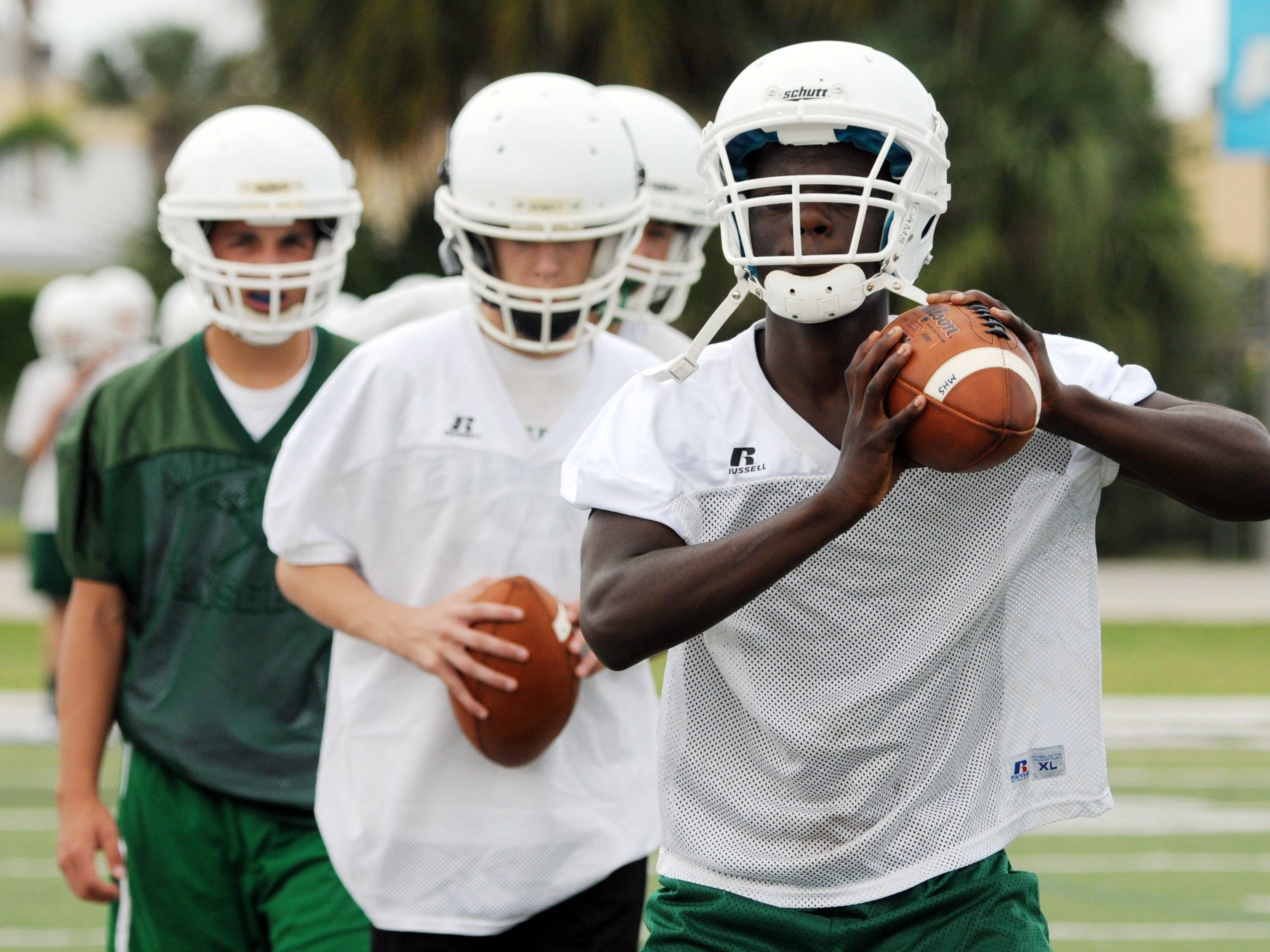 Potential quarterbacks go through agility drills during spring football practice this month in Melbourne.